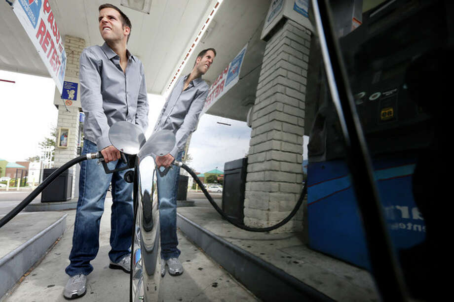 Ryan Goodman fills up his car at a gas station Friday, Oct. 5, 2012, in San Diego. Californians woke up to a shock Friday as overnight gasoline prices jumped by as much as 20 cents a gallon in some areas, ending a week of soaring costs that saw some stations close and others charge record prices. The average price of regular gas across the state was nearly $4.49 a gallon, the highest in the nation, according to AAA's Daily Fuel Gauge report. (AP Photo/Gregory Bull) / AP