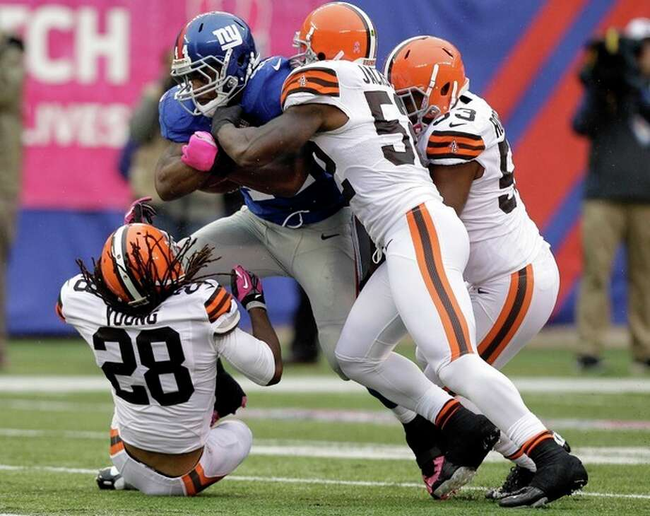 New York Giants running back Ahmad Bradshaw (44) is tackled by Cleveland Browns middle linebacker D'Qwell Jackson (52), Craig Robertson (53) and Usama Young (28) during the first half of an NFL football game Sunday, Oct. 7, 2012, in East Rutherford, N.J. (AP Photo/Kathy Willens) / AP