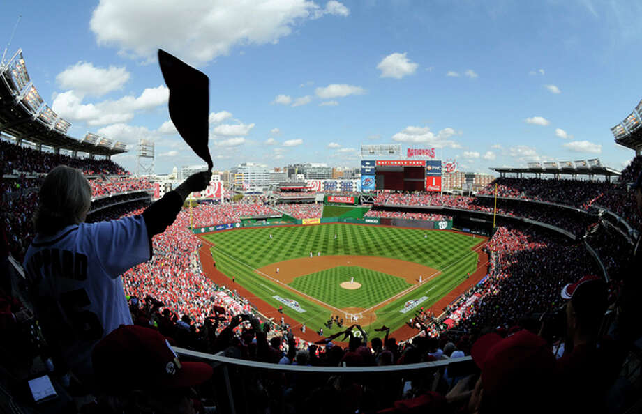 A fan waves a towel in the stands during Game 3 of the National League division baseball series between the Washington Nationals and the St. Louis Cardinals on Wednesday, Oct. 10, 2012, in Washington. (AP Photo/Nick Wass) / FR67404 AP