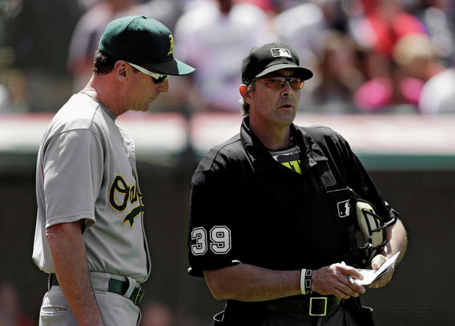 Oakland Athletics manager Bob Melvin goes over a lineup change with home plate umpire Paul Nauert (39) in the seventh inning of a baseball game against the Cleveland Indians, Thursday, May 9, 2013, in Cleveland. (AP Photo/Mark Duncan) / AP