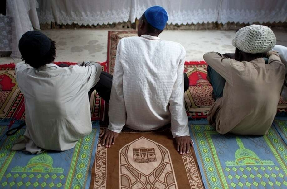 In this Sept. 28, 2012 photo, Muslim men sit on prayer rugs at the Al-Fattah Mosque during a Friday prayer service in Gressier, Haiti. Islam has won a growing number of followers in this impoverished country, especially after the catastrophic earthquake in 2010 that killed hundreds of thousands and left millions more homeless. (AP Photo/Dieu Nalio Chery) / AP