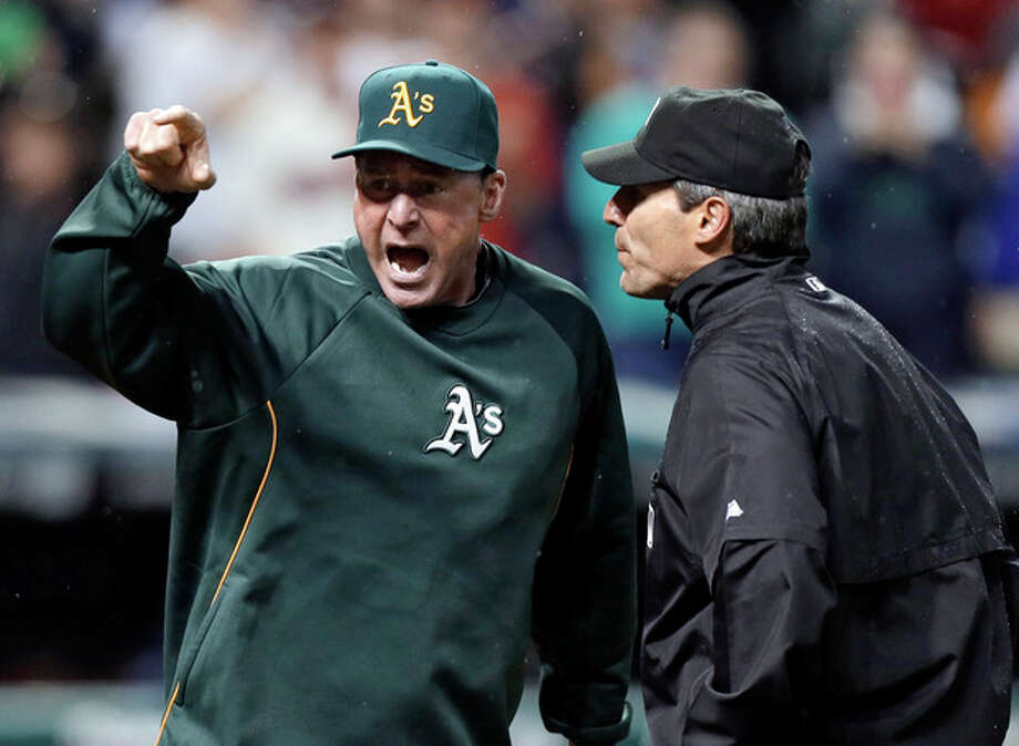 Oakland Athletics manager Bob Melvin, left, argues with umpire Angel Hernandez after a review failed to turn a double by Adam Rosales into a home run in the ninth inning of the A's baseball game against the Cleveland Indians on Wednesday, May 8, 2013, in Cleveland. Melvin was ejected. The Indians won 4-3. (AP Photo/Mark Duncan) / AP