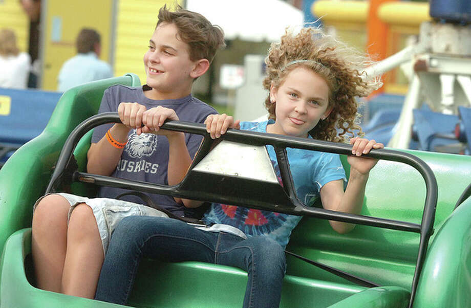 Hour Photo/Alex von Kleydorff 11yr old Matthew and 9yr old Samantha Zeller ride the Sizzler at the Rowayton Carnival on Friday night. / 2013 The Hour Newspapers