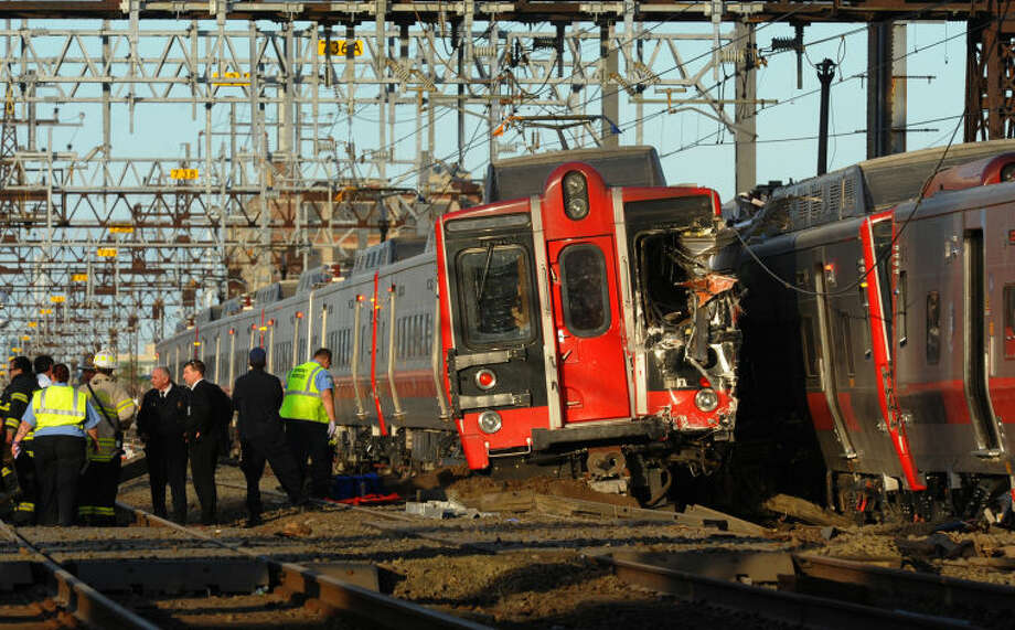 Emergency workers arrive at the scene of a train collision, Friday, May 17, 2013 in Fairfield, Conn. A New York-area commuter railroad says two trains have collided in Connecticut. The railroad says the accident involved a New York-bound train leaving New Haven. It derailed and hit a westbound train near Fairfield, Conn. Some cars on the second train also derailed. (AP Photo/The Connecticut Post, Christian Abraham) MANDATORY CREDIT