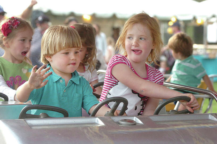 Hour Photo/Alex von Kleydorff 2yr old William Morris and 5yr old Elsa Holmes wave and drive on the Kiddie Combo at Roton School Rowayton Carival. It continues rain or shine on Saturday / 2013 The Hour Newspapers