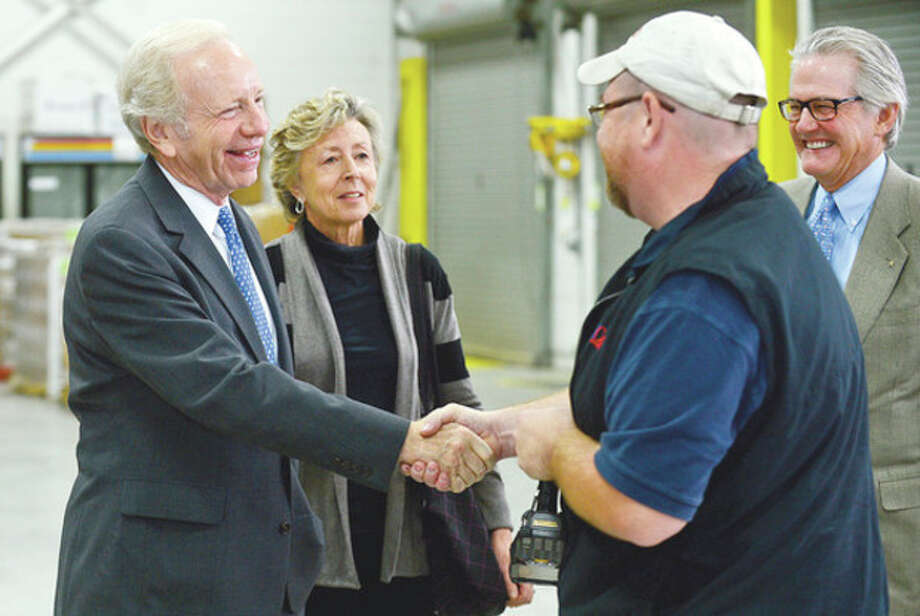 Hour photo / Erik TrautmannOutgoing U.S. Sen. Joe Lieberman, I-Conn., tours AmeriCares headquarters in Stamford Wednesday with his wife, Hadassah, and AmeriCares CEO, Curt Welling, where he greeted warehouse manager Dennis Brown Wednesday. / (C)2012, The Hour Newspapers, all rights reserved