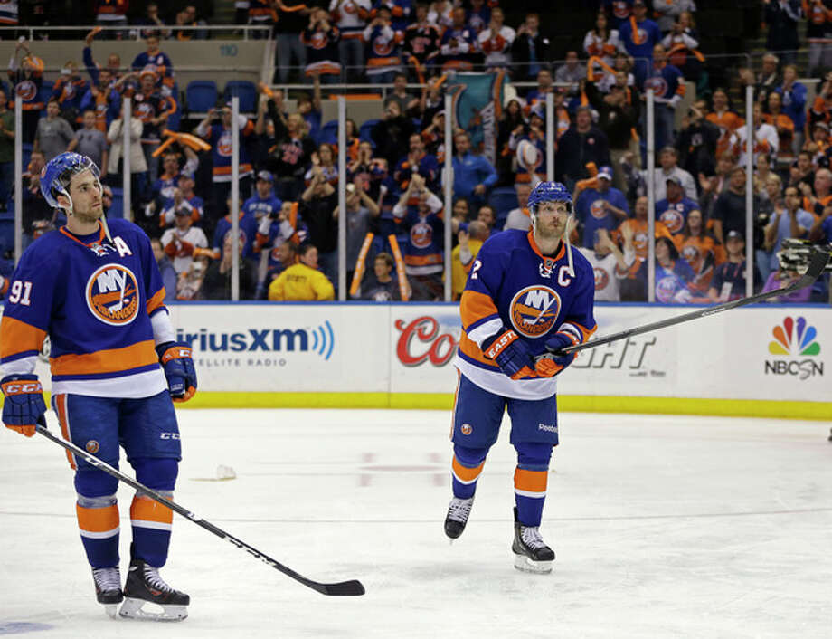 New York Islanders center John Tavares (91) and defenseman Mark Streit (2) react as the crowd applauds Islanders' season after the Pittsburgh Penguins defeated the Islanders 4-3 in overtime of Game 6 of a first-round NHL Stanley Cup playoff hockey series in Uniondale, N.Y., Saturday, May 11, 2013. The Penguins advanced to the Eastern Conference semifinals. (AP Photo/Kathy Willens) / AP