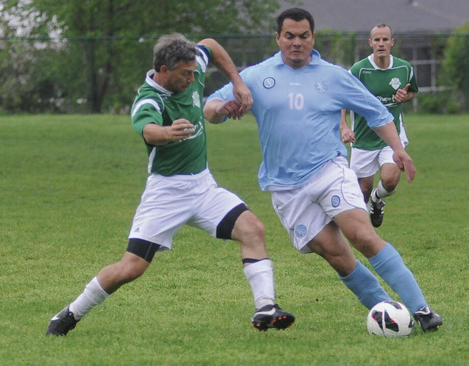 Hour photo/Matthew VinciNorwalk's Julio Camboa, right, beats New Britain's Brian Colby to the ball during Sunday morning's State Cup Soccer Over-40 semifinal game at the Coleytown Middle School in Westport.