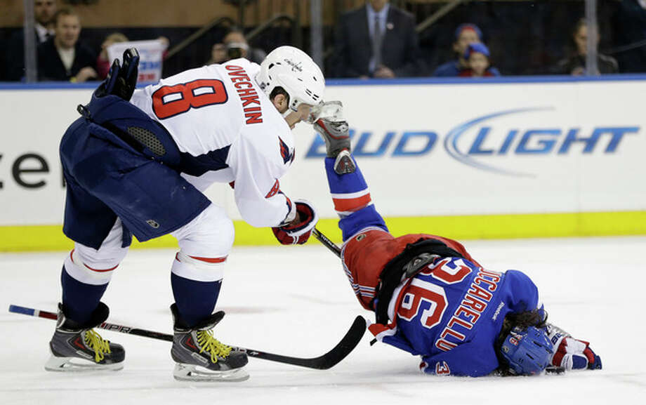 New York Rangers right wing Mats Zuccarello (36), of Norway, flips and hits the puck with his head in front of Washington Capitals left wing Alex Ovechkin (8), of Russia, in the second period of Game 6 of their NHL Stanley Cup hockey playoff series in New York, Sunday, May 12, 2013. (AP Photo/Kathy Willens) / AP