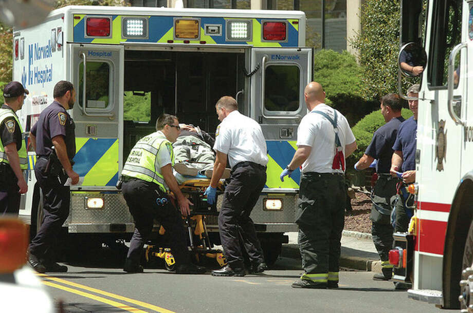 Hour Photo/Alex von Kleydorff A person is loaded into an ambulance for transport to Norwalk Hospital after being hit by a car on Van Zant st / 2013 The Hour Newspapers