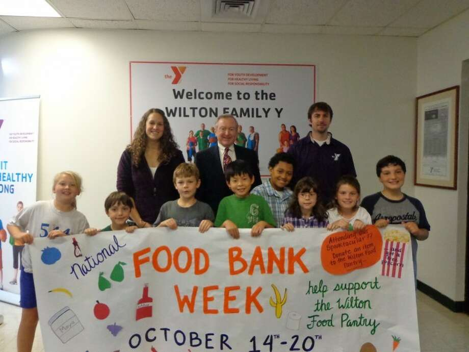 Pictured in the Y lobby with the National Food Bank display left to right are: Y Afterschool & Teen Director Laura Koellmer, First Selectman Bill Brennan, and Y Afterschool & Teen Director Geoff Malyszka with Y's Neighborhood Club program participants left to right Mairead Kehoe, Christian Stella, Shawn Heggland, Ben Lin, Kyle Roberts, Emily Wetzel, Sloan Barker, and Danta Stella.
