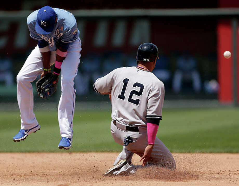 New York Yankees' Vernon Wells (12) steals second as Kansas City Royals shortstop Alcides Escobar misses an error thrown by catcher Salvador Perez during the fifth inning of a baseball game on Sunday, May 12, 2013, in Kansas City, Mo. (AP Photo/Charlie Riedel) / AP