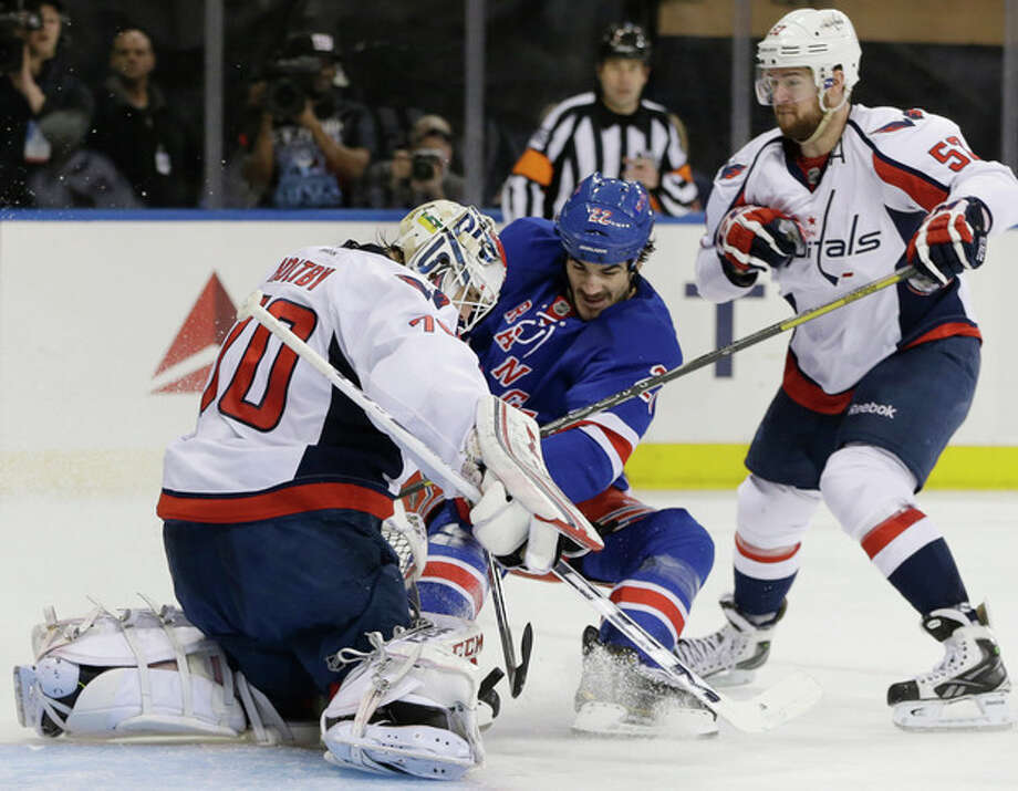 New York Rangers center Brian Boyle (22) takes a shot as Washington Capitals goalie Braden Holtby (70) defends and Washington Capitals defenseman Mike Green (52) looks on in the second period of Game 6 of their NHL Stanley Cup hockey playoff series in New York, Sunday, May 12, 2013. (AP Photo/Kathy Willens) / AP