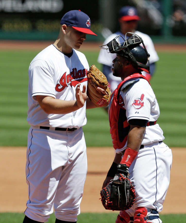 Cleveland Indians starting pitcher Justin Masterson, left, talks with catcher Carlos Santana in the fifth inning in the first baseball game of a doubleheader against the New York Yankees, Monday, May 13, 2013, in Cleveland. (AP Photo/Tony Dejak) / AP
