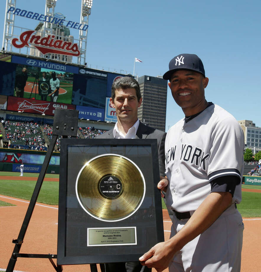 New York Yankees relief pitcher Mariano Rivera holds up a Rock Hall plaque given to him by the Cleveland Indians between the first and second baseball games of a doubleheader, Monday, May 13, 2013, in Cleveland. (AP Photo/Tony Dejak) / AP