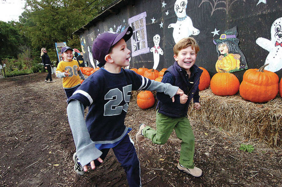 Hour photo / Alex von KleydorffPre-Halloween funFrom left: John Insinga, 6, and Jack Miller, 5, run to go back through the Haunted House a few more times with Vincent Insinga catching up during fall activities Monday at the Eden Farms nursery and garden center on Stillwater Road in Stamford. The center also offers hay rides, pumpkin carving and pony rides. / 2012 The Hour Newspapers