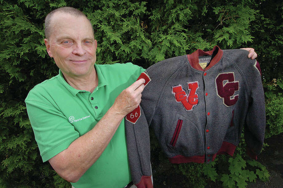 Hour photo/Alex von KleydorffTim Bishop holds the varsity jacket he was awarded for his efforts at Central Catholic High School. A 1966 graduate of CCHS, Bishop was a standout in three sports for the Cavaliers. / 2013 The Hour Newspapers