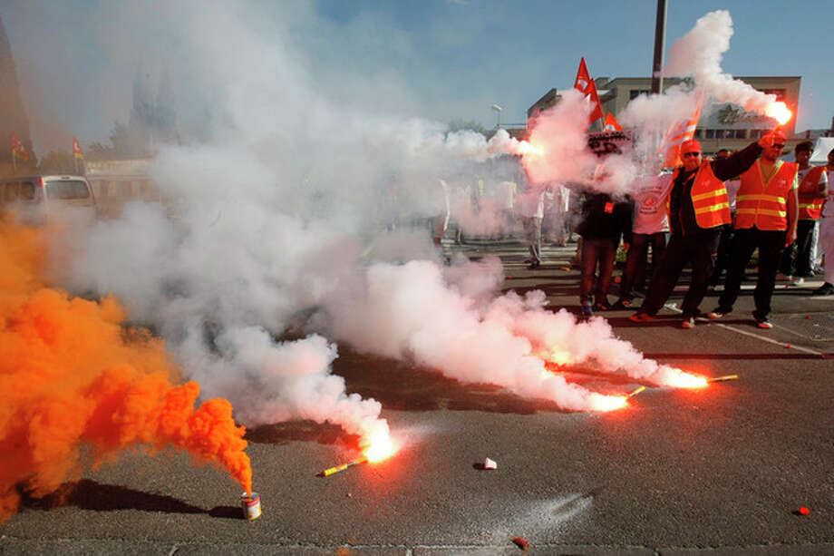 Employees of Arkema Kem One chemical company and employees of other petrochemical sites, burn flares as they block the Arkema plant in Marseille, southern France, Tuesday, May 14 , 2013. Kem One, the maker of vinyl products announced last July it may cuts jobs. (AP Photo/Claude Paris) / AP