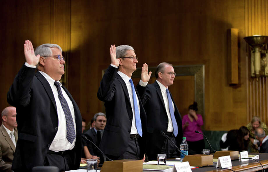 Apple CEO Tim Cook, center, flanked by Peter Oppenheimer, Apple's chief financial officer, left, and Phillip A. Bullock, Apple's head of Tax Operations, are sworn in on Capitol Hill in Washington, Tuesday, May 21, 2013, prior to testifying before the Senate Homeland Security and Governmental Affairs Permanent subcommittee on Investigations hearing to examine the methods employed by multinational corporations to shift profits offshore and how such activities are affected by the Internal Revenue Code. Apple, the world's most valuable company, based in Cupertino, Calif., holds a billion dollars in an Irish subsidiary as a tax strategy, according to a report issued this week by the subcommittee. (AP Photo/J. Scott Applewhite) / AP