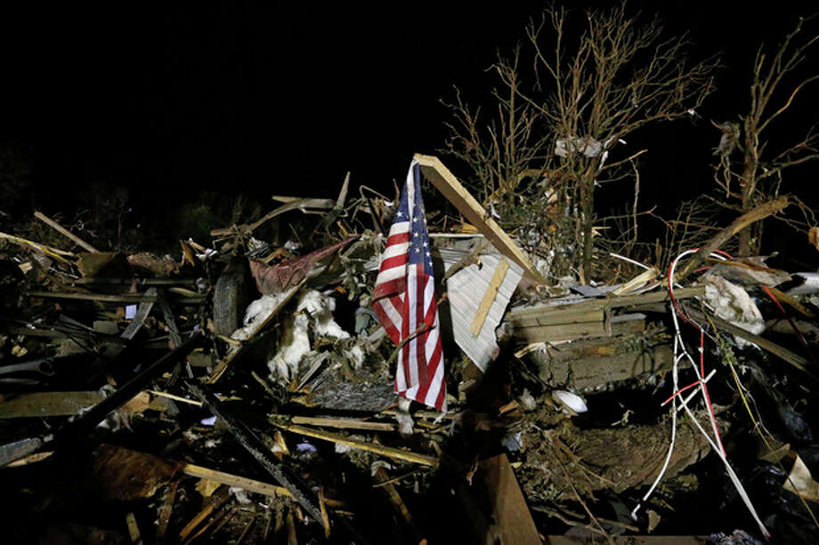 A flag flies in the debris of a mobile home after a tornado struck a mobile home park near Dale, Okla., Sunday, May 19, 2013. (AP Photo Sue Ogrocki) / AP