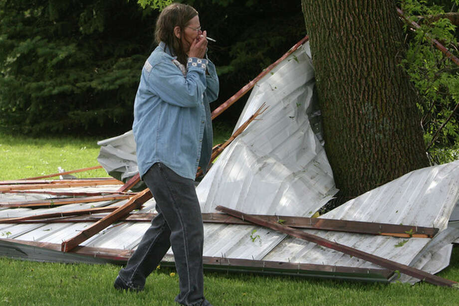 June McFarland reacts to the first sight of storm damage in rural Osage, Iowa on Sunday, May 19, 2013. A powerful weather system moved through the area on Sunday afternoon triggering tornado warnings, high winds and hail. (AP Photo/The Globe Gazette, Arian Schuessler) / Mason City Globe Gazette
