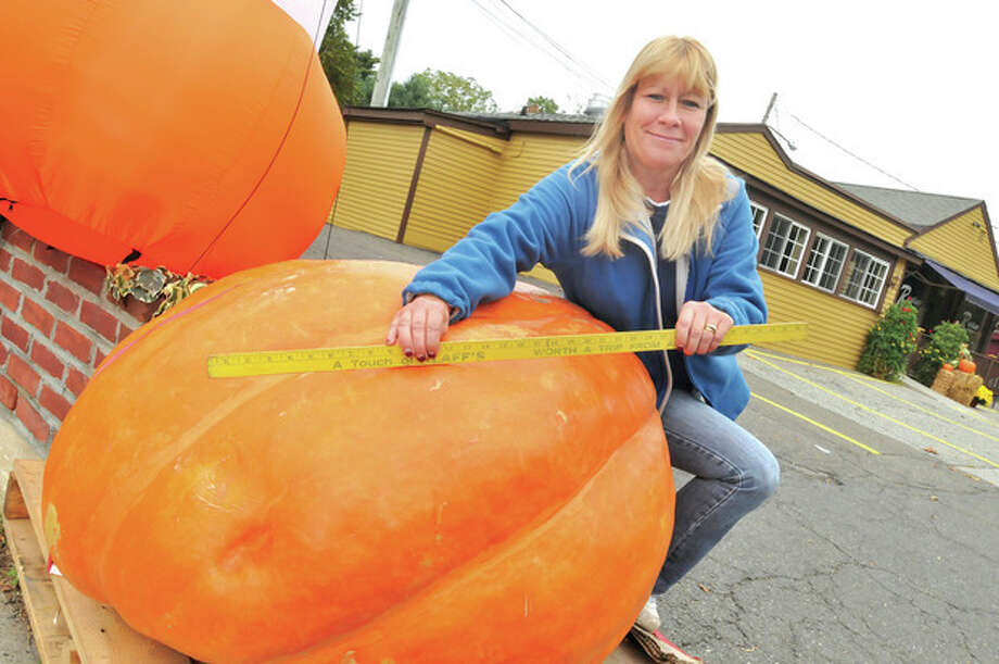 Nancy Purcell with Izzo + Son County Garden in Westport with a 713 pound pumkin that will be raffled off and the proceeds going to breast cancer research. hour photo/Matthew Vinci