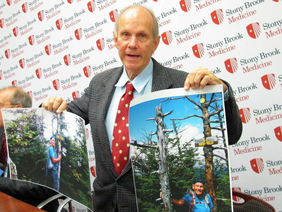 Stony Brook University professor Michael T. Vaughan holds up photographs he took during a summer camping trip as he speaks with reporters at Stony Brook University Hospital in Stony Brook, N.Y. on Friday, Oct. 12, 2012. Doctors are awaiting test results to confirm whether Vaughan may have contracted the hantavirus during the camping trip. (AP Photo/Frank Eltman) / AP
