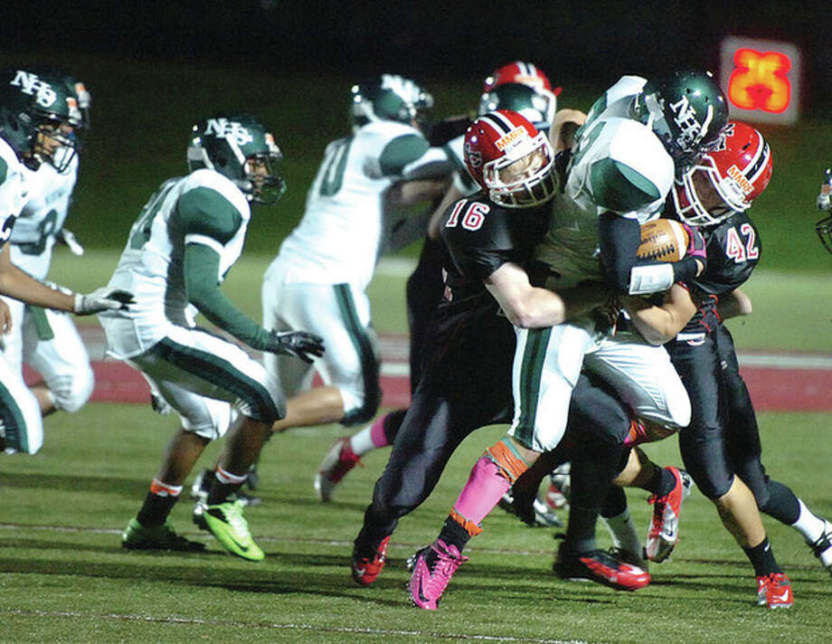 Hour photo/Alex von KleydorffNorwalk's Danny Jakab is wrapped up by a bevy of New Canaan defenders including Kyle McEneaney (16) and Thomas Costigan (42) during Friday night's game at Dunning Field. / 2012 The Hour Newspapers