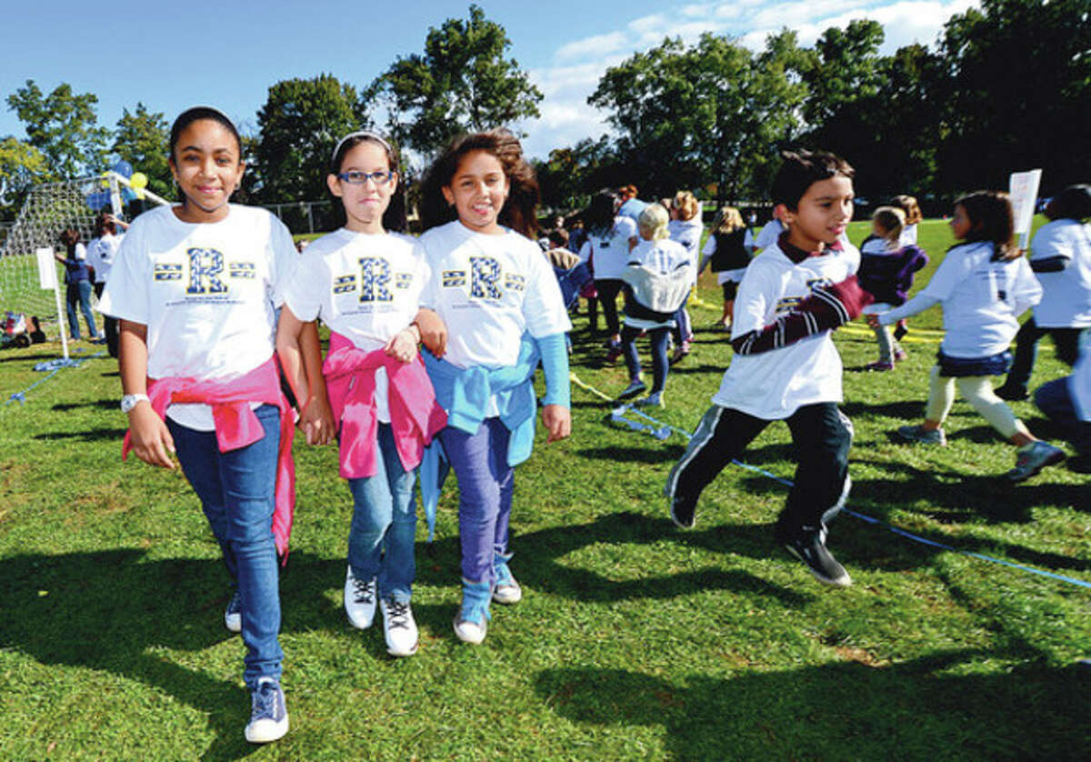 Students at Rowayton Elementary School students including 5th graders Karlys Nesa, Jadis Vigo and Natalie Ramosconduct their walk-a-thon Friday that raised nearly $20,000 for a new computer lab. Hour photo / Erik Trautmann