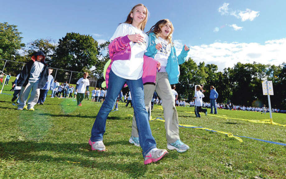 Students at Rowayton Elementary School students including 5th graders Tess Jordan and Claire Morrow conduct their walk-a-thon Friday that raised nearly $20,000 for a new computer lab.Hour photo / Erik Trautmann / (C)2012, The Hour Newspapers, all rights reserved
