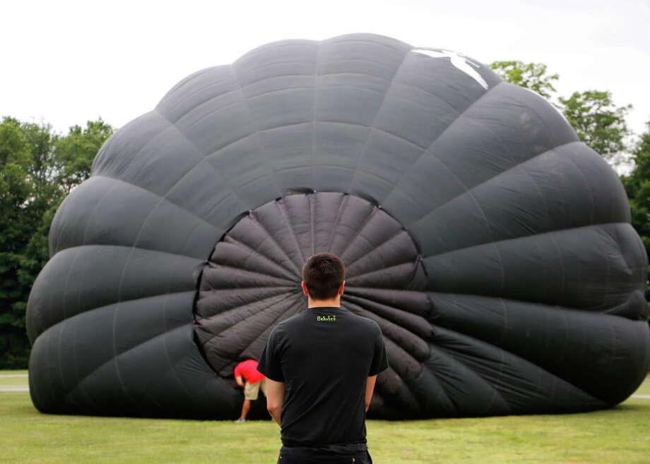 Jake Frame, 19, from Pennsylvania helps inflate the Wicked balloon at Saratoga County Fairgrounds on Thursday, June 18, 2015, in Ballston Spa, N.Y. The Saratoga Balloon and Craft Festival will take place here from June 19-21 and offers balloon launches and glows, a juried Art & Craft section, kids activities, live entertainment, and food and beverages. (Olivia Nadel/ Special to the Times Union) Photo: ON / 00032227A