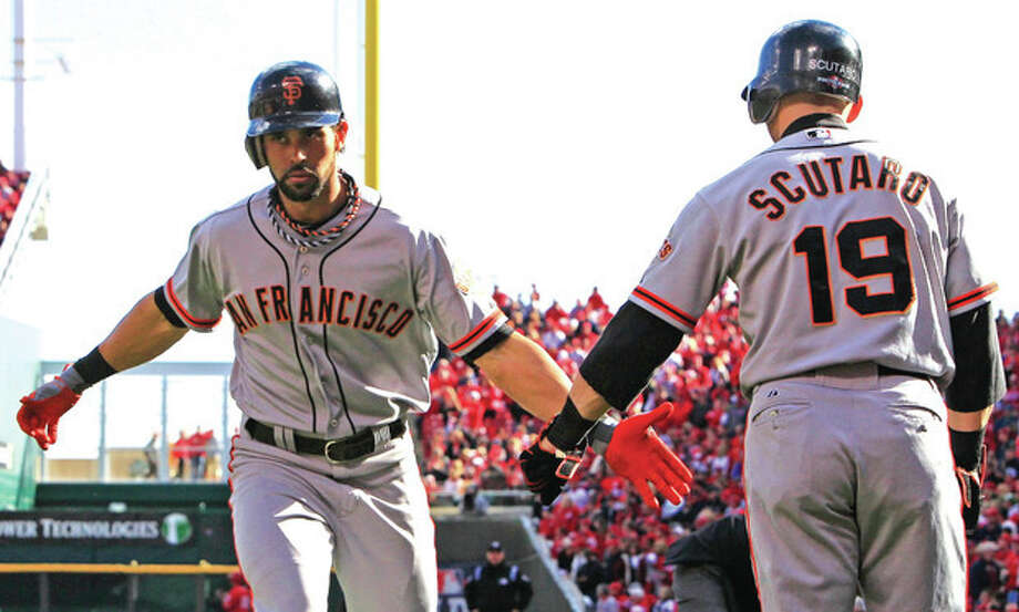 AP photoAngel Pagan, left, is congratulated by teammate Marco Scutaro after hitting a first inning homer that got the San Francisco Giants started toward an 8-3 victory over the Cincinnati Reds in Game 4 of their NLDS clash. / AP