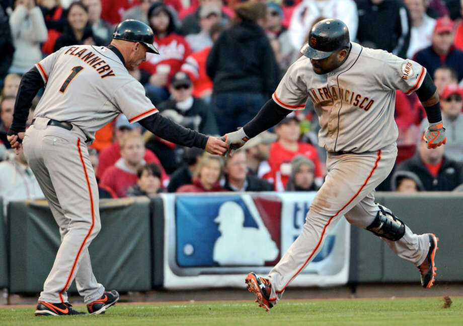 San Francisco Giants' Pablo Sandoval is congratulated by third base coach Tim Flannery (1) after hitting a two-run home run against the Cincinnati Reds in the seventh inning of Game 4 of the National League division baseball series, Wednesday, Oct. 10, 2012, in Cincinnati. (AP Photo/Michael Keating) / FR170759 AP