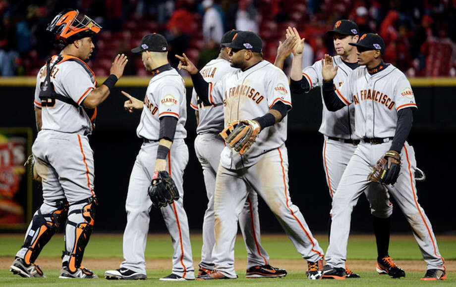 San Francisco Giants players celebrate after defeating the Cincinnati Reds 8-3 in Game 4 of the National League division baseball series, Wednesday, Oct. 10, 2012, in Cincinnati. (AP Photo/Michael Keating) / FR170759 AP