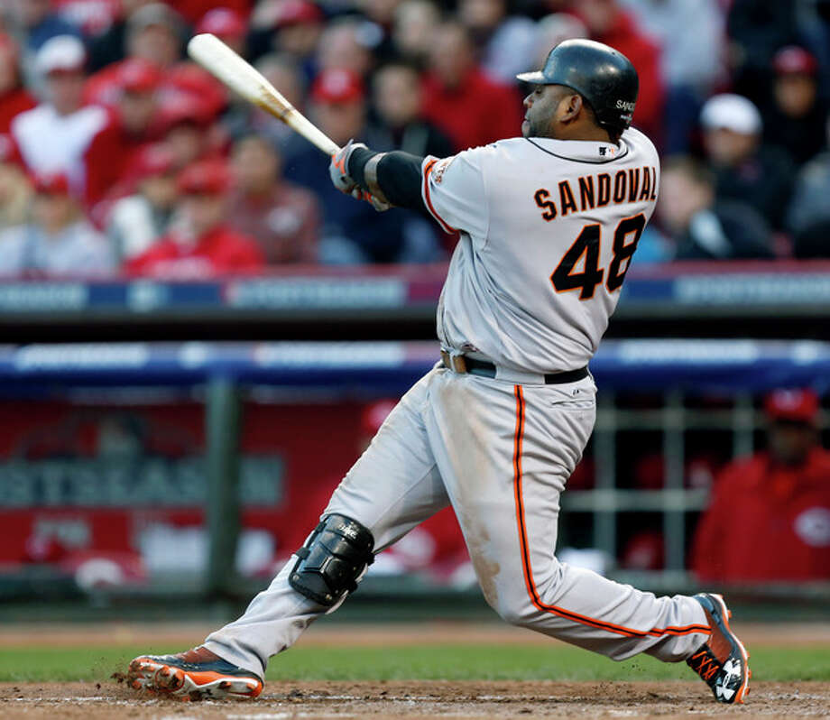 San Francisco Giants' Pablo Sandoval hits a two-run home run in the seventh inning of Game 4 of the National League division baseball series against the Cincinnati Reds, Wednesday, Oct. 10, 2012, in Cincinnati. (AP Photo/David Kohl) / FR51830 AP