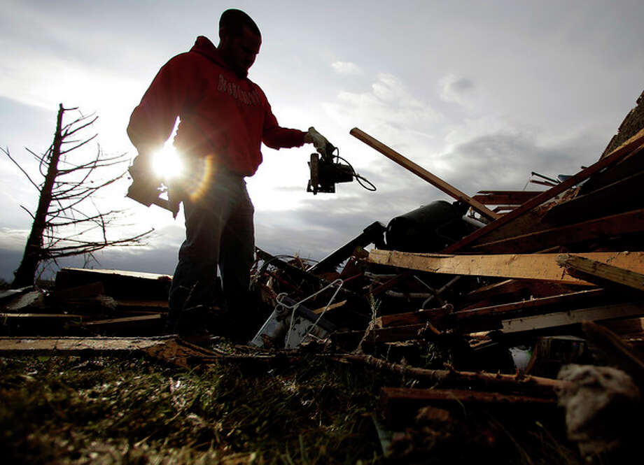 Zac Woodcock salvages items from the rubble of a tornado-ravaged rental home which they own Tuesday, May 21, 2013, in Moore, Okla. A huge tornado roared through the Oklahoma City suburb Monday, flattening an entire neighborhoods and destroying an elementary school with a direct blow as children and teachers huddled against winds. (AP Photo/Charlie Riedel) / AP