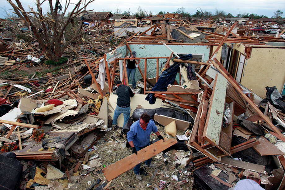 Jimmy Hodges helps Chad Heltcel and his wife Cassidi salvage the wreckage of Chad Heltcel's family home, which was destroyed Monday when a tornado moved through Moore, Okla., Tuesday, May 21, 2013. The huge tornado roared through the Oklahoma City suburb, flattening entire neighborhoods and destroying an elementary school with a direct blow as children and teachers huddled against winds.(AP Photo/Brennan Linsley) / AP
