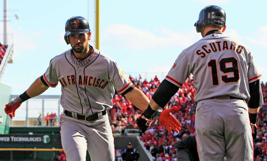 San Francisco Giants' Angel Pagan is congratulated by Marco Scutaro (19) after Pagan hit a solo home run in the first inning of Game 4 of the National League division baseball series against the Cincinnati Reds, Wednesday, Oct. 10, 2012, in Cincinnati. (AP Photo/Al Behrman) / AP