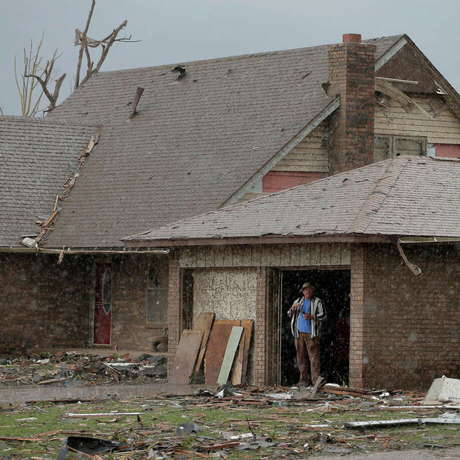 An unidentified man watches a rain storm from inside the garage of his tornado-damaged home Tuesday, May 21, 2013, in Moore, Okla. A huge tornado roared through the Oklahoma City suburb Monday, flattening entire neighborhoods and destroying an elementary school with a direct blow as children and teachers huddled against winds. (AP Photo/Charlie Riedel) / AP