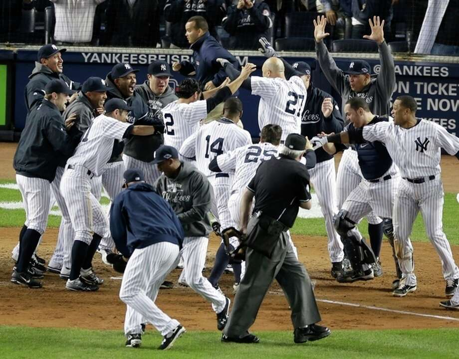 New York Yankees' Raul Ibanez (27) is mobbed by teammates at home plate after he hit the game-winning home run in the 12th inning in Game 3 of the American League division baseball series against the Baltimore Orioles on Wednesday, Oct. 10, 2012, in New York. The Yankees won 3-2. (AP Photo/Peter Morgan) / AP
