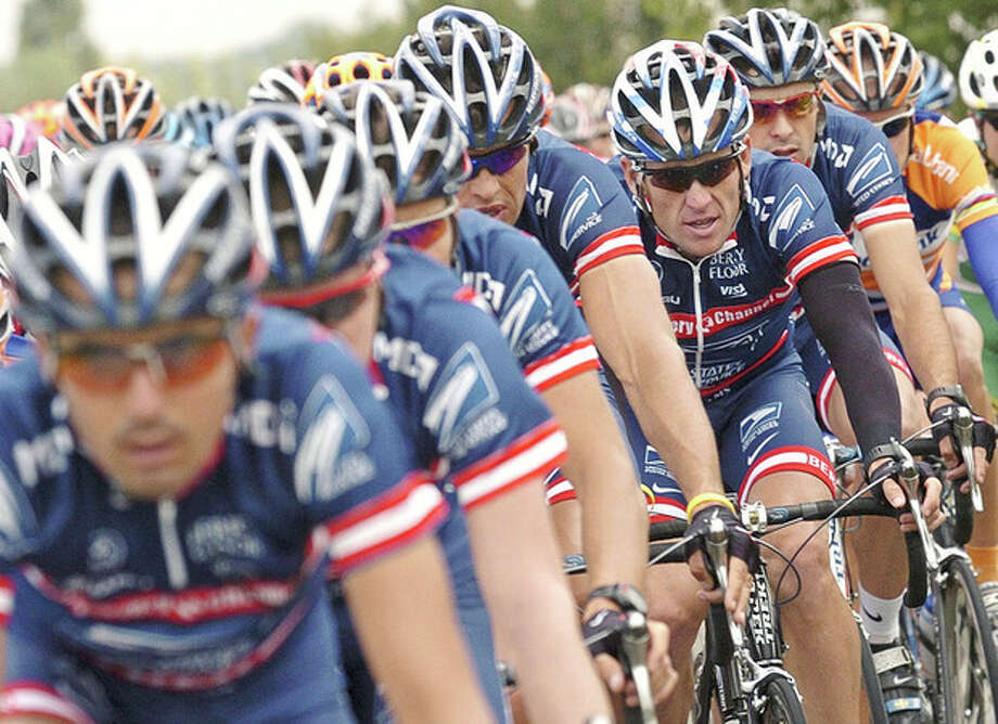 "FILE - This July 5, 2004 file photo shows U.S. Postal Service team leader and five-time Tour de France winner Lance Armstrong, third from right, framed by his teammates as the pack rides during the second stage of the 91st Tour de France cycling race between Charleroi and Namur, Belgium. The U.S. Anti-Doping Agency says 11 of Lance Armstrong's former teammates testified against him in its investigation of the cyclist, revealing ""the most sophisticated, professionalized and successful doping program that sport has ever seen."" USADA will deliver its reasoned decision against Armstrong later Wednesday, Oct. 10, 2012, a summary of the facts it used to hand him a lifetime suspension and erase his seven Tour de France titles. (AP Photo/Christophe Ena, File) / AP"