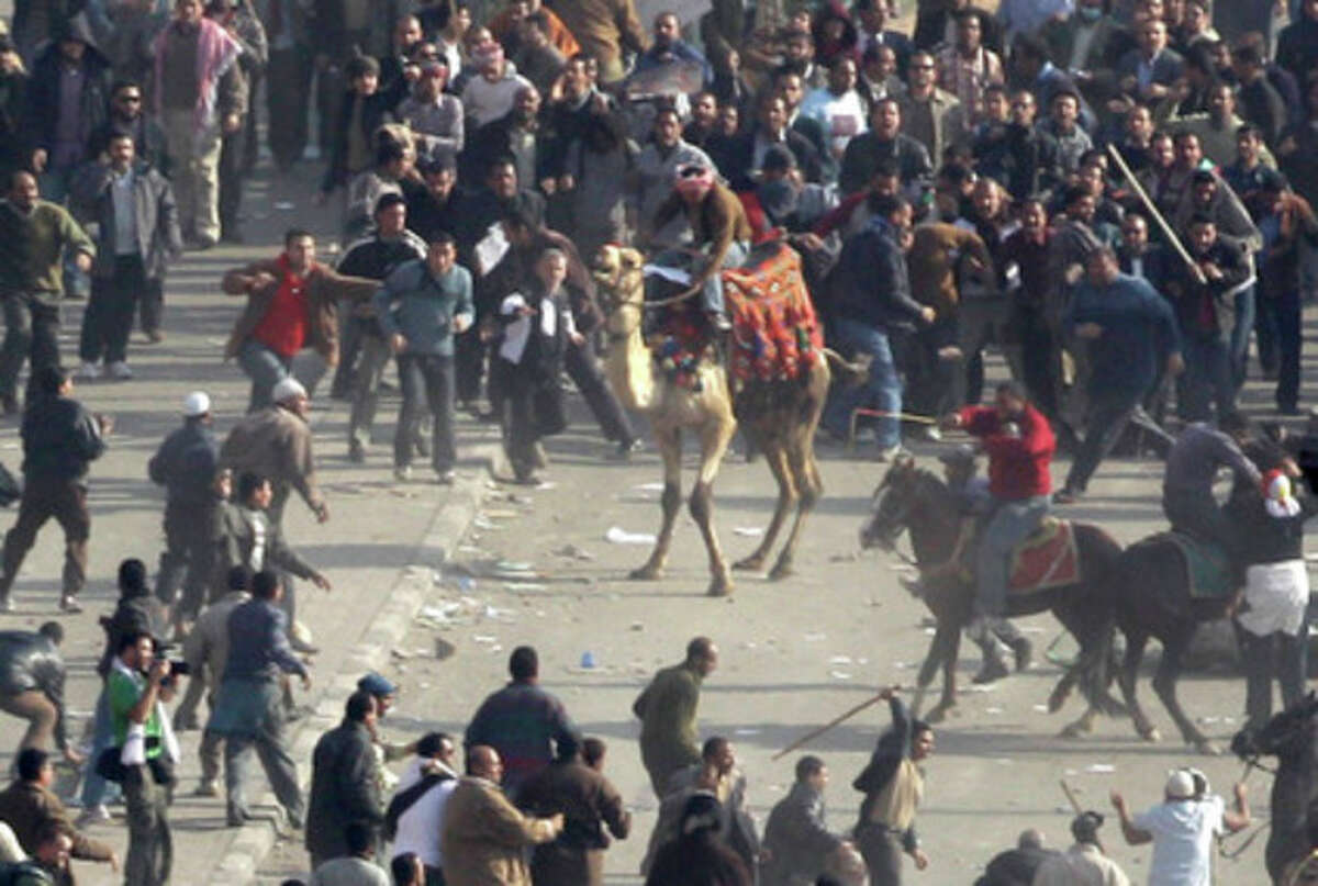 FILE - In this Wednesday, Feb. 2, 2011 file photo, pro-government demonstrators, some riding camels and horses and armed with sticks, clash with anti-government demonstrators in Tahrir square, the center of anti-government demonstrations, in Cairo, Egypt. Egypt's state news agency said Wednesday, Oct. 10, 2012 that a Cairo court has acquitted 25 loyalists of ousted President Hosni Mubarak loyalists who had been accused of organizing an attack in which assailants on horses and camels charged into crowds of anti-regime protesters last year. (AP Photo/Ben Curtis, File)