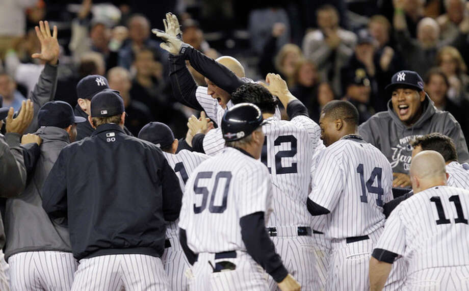 New York Yankees' Raul Ibanez celebrates with teammates as he reaches home plate after hitting the game-winning home run during the 12th inning of Game 3 of the American League division baseball series against the Baltimore Orioles on Wednesday, Oct. 10, 2012, in New York. The Yankees 3-2. (AP Photo/Kathy Willens) / AP