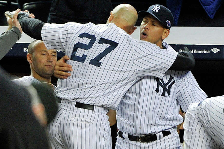 New York Yankees' Alex Rodriguez, right, hugs Raul Ibanez (27) as Derek Jeter watches at left after Ibanez pinch-hit a home run in place of Rodriguez during the ninth inning of Game 3 of their American League division baseball series against the Baltimore Orioles, Wednesday, Oct. 10, 2012, in New York. The Yankees won 3-2. (AP Photo/Bill Kostroun) / FR59151 AP