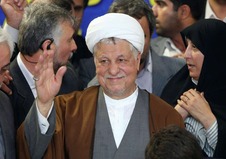 In this picture taken on Saturday, May 11, 2013, former Iranian President Akbar Hashemi Rafsanjani waves to media as he registers his candidacy for the upcoming presidential election, while his daughter Fatemeh, right, looks on, at the election headquarters of the interior ministry in Tehran, Iran. A hardline news website says Iran's election overseers have rejected a pair of powerful and divisive figures from running in next month's presidential election. Tasnimnews.com say Akbar Hashemi Rafsanjani, a former president who still wields enormous influence, and Esfandiar Rahim Mashaei, a close confident of President Mahmoud Ahmadinejad, have been barred by the Guardian Council. (AP Photo/Ebrahim Noroozi) / AP