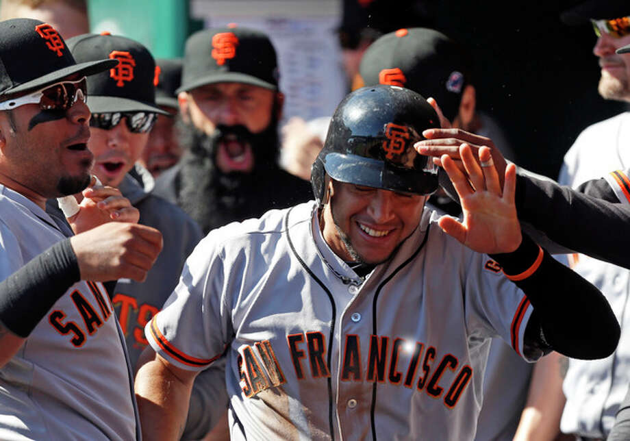 San Francisco Giants' Gregor Blanco, right, is congratulated in the dugout after scoring the first run of the game in the fifth inning of Game 5 of the National League division baseball series against the Cincinnati Reds, Thursday, Oct. 11, 2012, in Cincinnati. Blanco scored from first on an RBI triple by Brandon Crawford. (AP Photo/David Kohl) / FR51830 AP
