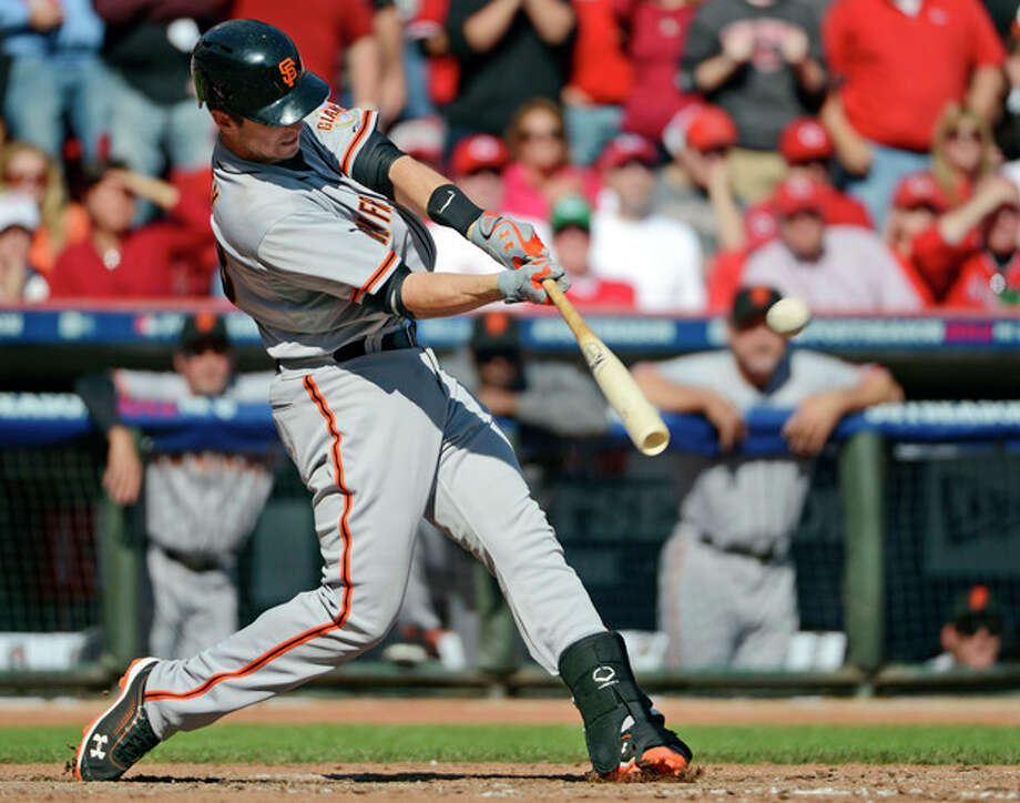 San Francisco Giants' Buster Posey hits a grand slam off Cincinnati Reds starting pitcher Mat Latos in the fifth inning of Game 5 of the National League division baseball series, Thursday, Oct. 11, 2012, in Cincinnati. (AP Photo/Michael Keating) / FR170759 AP