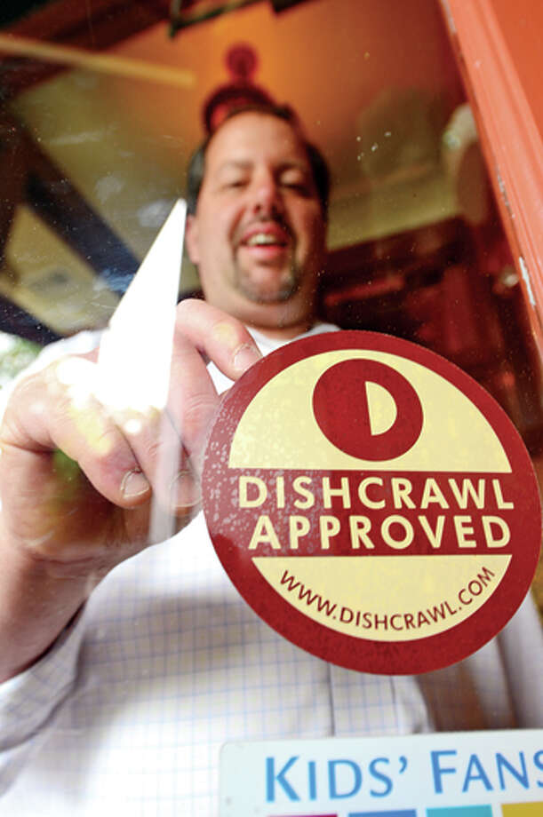 Michael Machetti owner of Columbus Park Trattoria puts in Dishcrawl sticker in his restaurant window. DishCrawl is an event where participants go to four different surprise restaurants over a two-hour span and sample dishes and listen to little history about the restaurants. The event comes to downtown Stamford for the first time thisTuesday. Hour photo / Erik Trautmann / (C)2013, The Hour Newspapers, all rights reserved