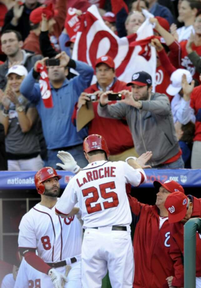 Washington Nationals' Adam LaRoche (25) high-fives teammates in the dugout after hitting a solo home run in the second inning of Game 4 of the National League division baseball series against the St. Louis Cardinals, Thursday, Oct. 11, 2012, in Washington. (AP Photo/Nick Wass)