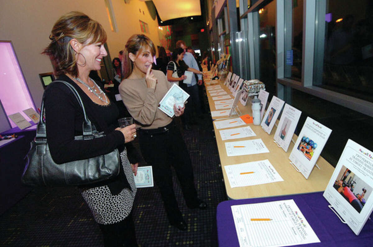 Hour Photo Alex von Kleydorff; l-r Stacey Brekke and Ronnie Stanford bid on silent auction items up for grabs at Norwalk reads fundraiser gala at Stepping Stones.